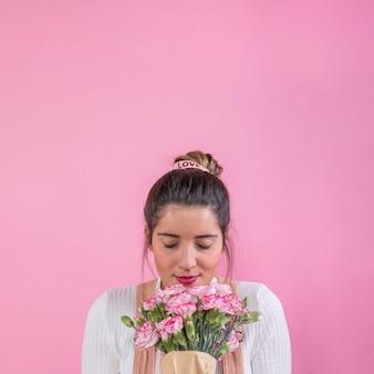 Femme, sentant, bouquet fleurs