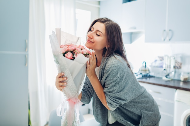 Femme sentant le bouquet de roses. femme au foyer en appréciant le décor et l'intérieur de la cuisine.