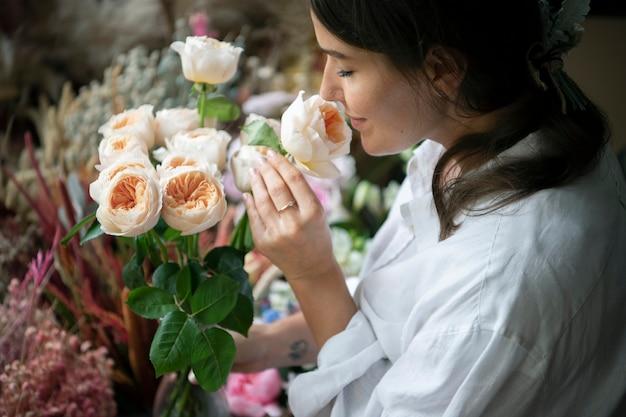 Femme sentant un bouquet de roses romantiques vuvuzela.