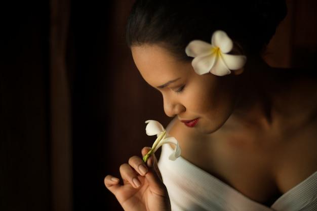 Femme sentant une fleur blanche à proximité