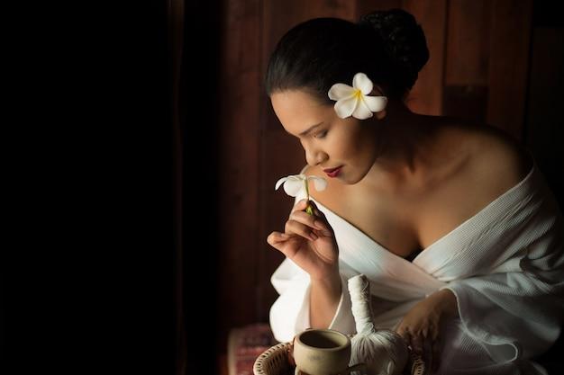 Femme sentant une fleur blanche