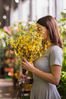 Femme sentant les fleurs jaunes