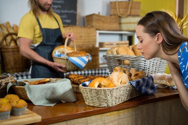 Femme sentant un pain au comptoir