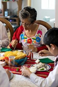 Une femme sentant un piment de la main d'un enfant, assise à une table