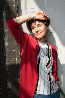 Femme sereine dans des vêtements décontractés élégants debout par le mur en face de la fenêtre sur une journée ensoleillée et profiter d'être seule