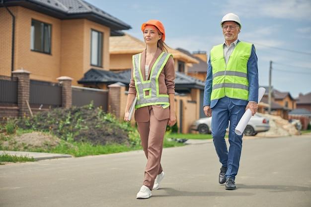 Femme sereine et un ingénieur civil sérieux marchant le long de la rue