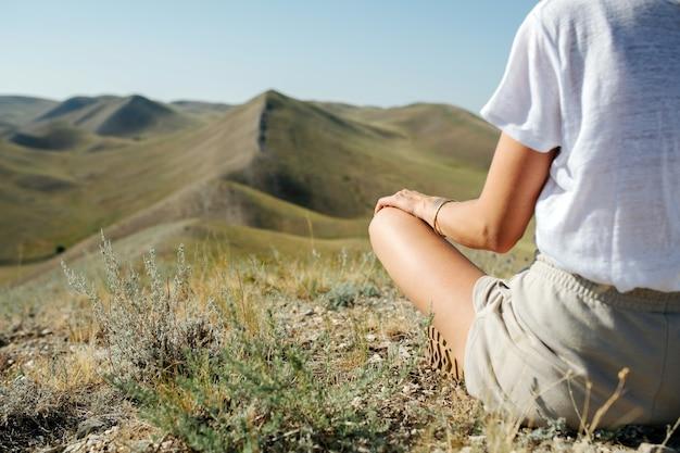 Femme sereine méditant, profitant de beaux paysages, admirant une vue imprenable sur les collines majestueuses qui s'étendent partout.