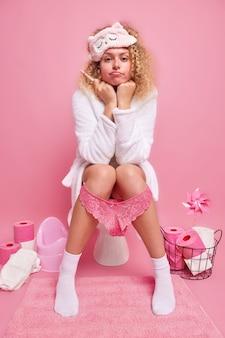 Une femme sérieuse aux cheveux bouclés attend le résultat du test de grossesse porte un masque de sommeil et un peignoir pose sur la cuvette des toilettes regarde directement devant elle va devenir mère
