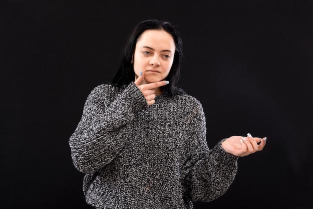 Femme sérieuse aux cheveux longs portant un pull gris gesticulant avec ses mains