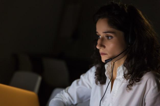 Femme sérieuse, à, casque à écouteurs, dans, bureau sombre
