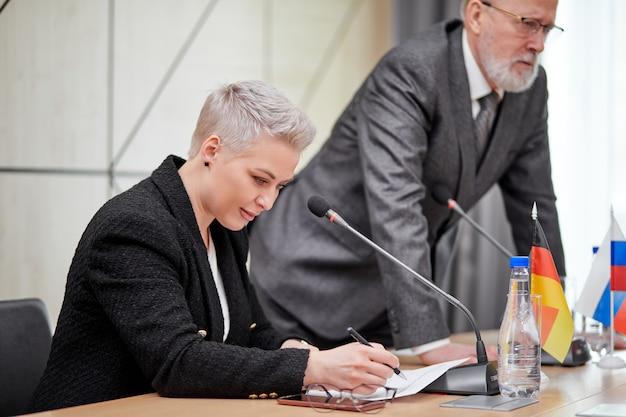 Femme sérieuse concentrée en costume à la conférence, écoutant les discussions des partenaires, lors d'une réunion multiethnique sans liens. entreprise, concept de sommet