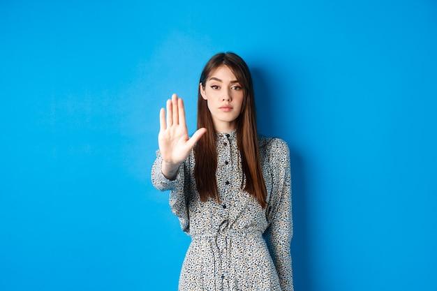 Femme sérieuse et confiante aux cheveux longs et à la robe, tendez la main et dites non, faites un geste d'arrêt, interdisez les mauvaises actions, debout sur le bleu