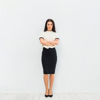Femme sérieuse dans des vêtements légers, debout avec les bras croisés