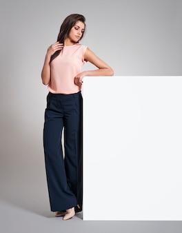 Femme sérieuse debout à côté du tableau blanc