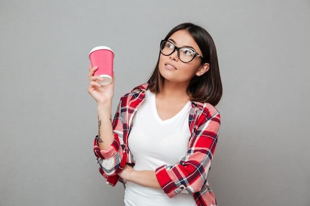 Femme sérieuse, debout sur un mur gris, tenant une tasse de café.