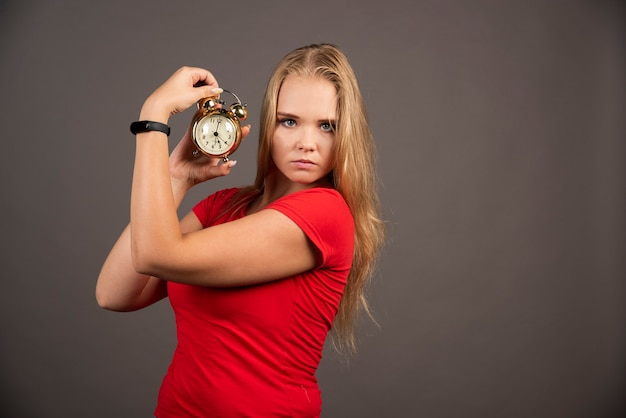 Femme sérieuse debout sur un mur noir avec horloge.
