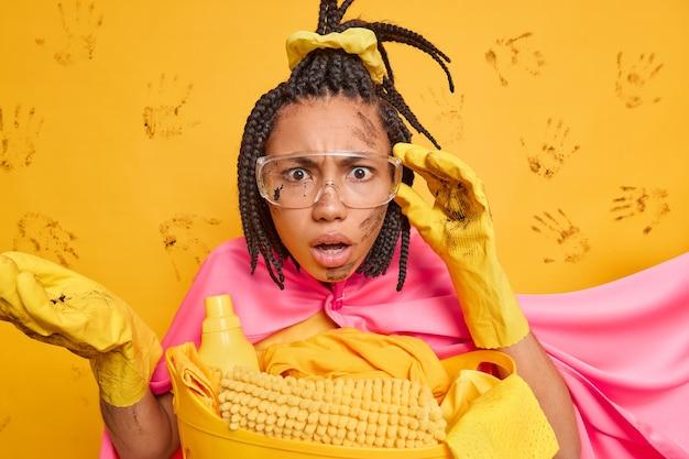 Une femme sérieuse et désordonnée avec des dreadlocks peignés étant sale après avoir rangé la pièce regarde attentivement à travers des lunettes transparentes porte un costume de super-héros isolé sur un mur jaune