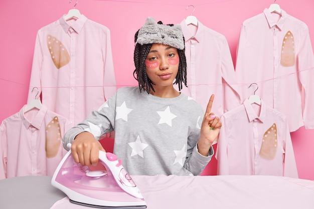 Une femme sérieuse avec des dreadlocks et des coussinets sous les yeux pointe l'index a une idée pose près des fers à repasser les vêtements donne un service de nettoyage. femme de ménage à domicile.