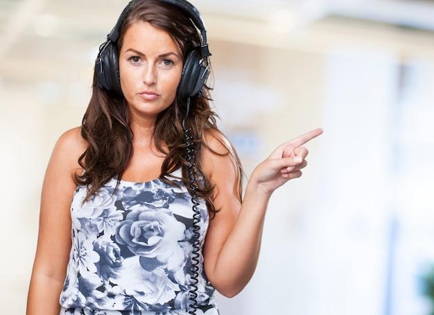 Femme sérieuse écouter de la musique et pointant vers la copyspace