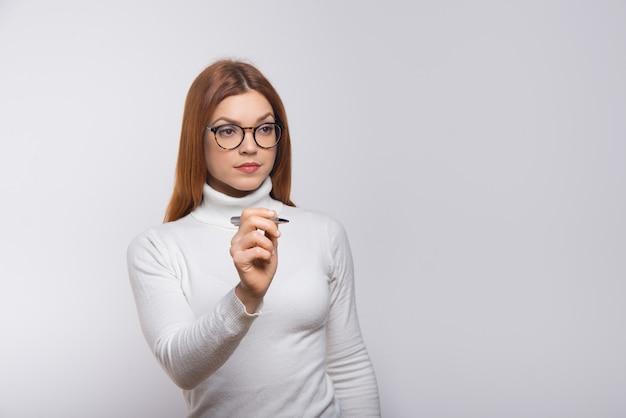 Femme sérieuse, écrire quelque chose dans l'air