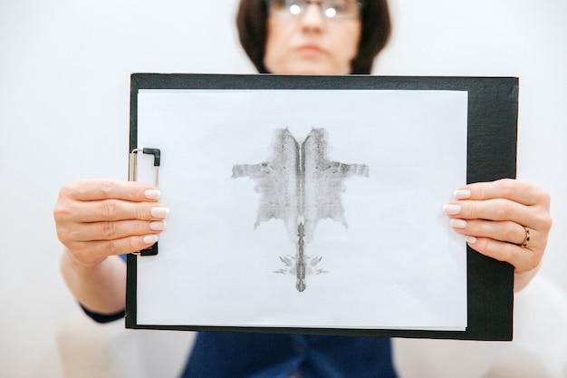 Une femme sérieuse est assise et montre une photo à la caméra. il est attaché à la tablette. elle le tient à deux mains. il est dessiné au crayon.
