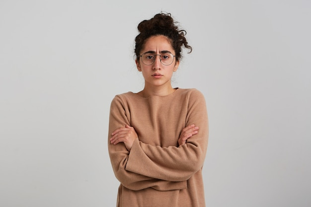 Femme sérieuse, fronçant les sourcils femme avec chignon cheveux bouclés foncés, portant des lunettes et pull beige