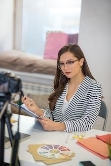 Femme sérieuse intelligente partageant ses connaissances tout en ayant une leçon vidéo