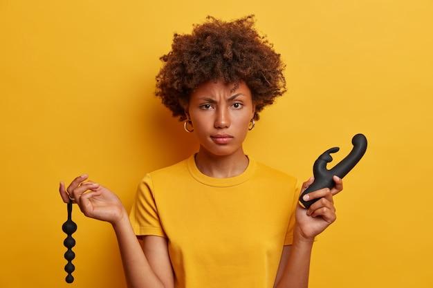 Une femme sérieuse et mécontente aux cheveux afro choisit entre des perles anales et un vibrateur dans un sex-shop, a besoin d'un outil pour la stimulation du clitoris et du point g, une pénétration agréable. orgasme et plaisir