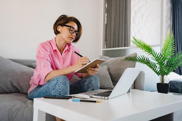 Femme sérieuse occupée en chemise rose assis concentré prendre des notes de payer des factures sur un canapé à la maison à table travaillant en ligne sur un ordinateur portable à la maison