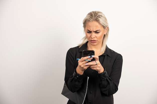 Femme sérieuse à la recherche sur téléphone mobile et tenant un presse-papiers. photo de haute qualité