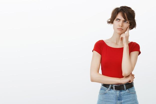 Femme sérieuse et réfléchie à la recherche dans le coin supérieur gauche avec visage dérangé en colère