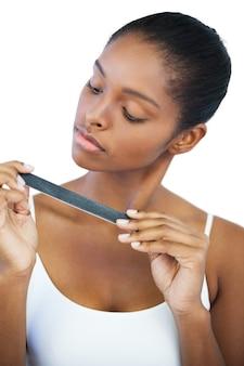Femme sérieuse en regardant sa lime à ongles