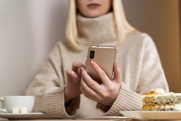 Femme sérieuse regardant téléphone intelligent vérifiant les nouvelles sur un café.