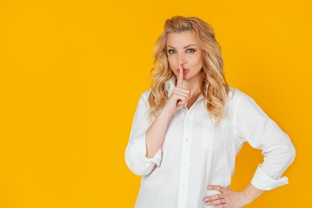 Une femme sérieuse regarde silencieusement et presse son index contre ses lèvres, fronçant les sourcils avec désapprobation