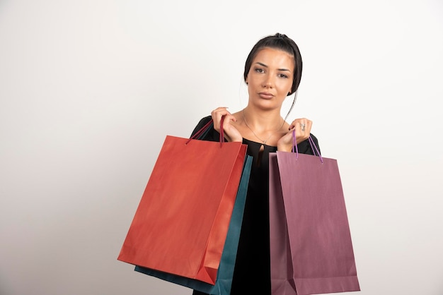 Femme sérieuse avec des sacs à provisions sur mur blanc.