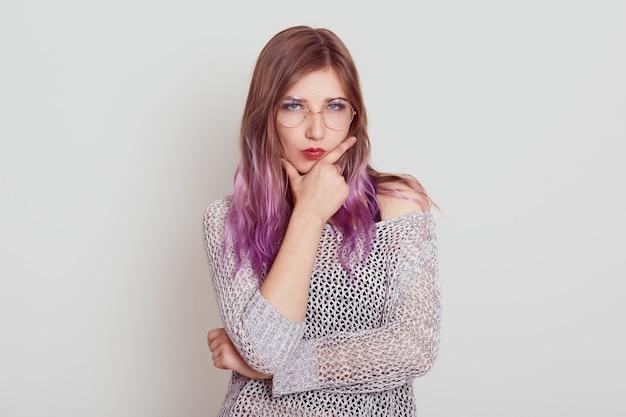 Femme sérieuse stricte aux cheveux lilas gardant les doigts dans son menton, pensant à des choses importantes ou à des problèmes, portant une chemise élégante, posant isolée sur un mur gris.