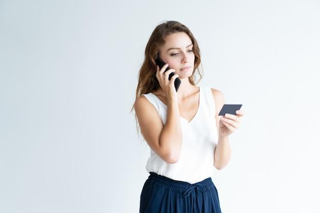 Femme sérieuse tenant une carte de crédit et parlant au téléphone mobile