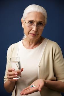 Femme sérieuse tenant des pilules.