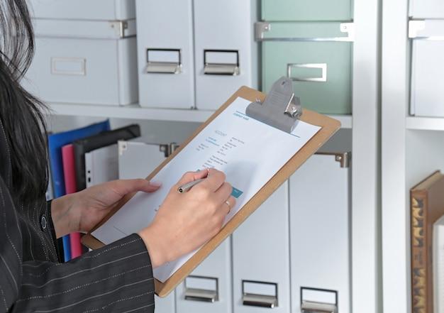 Femme sérieuse travaillant avec tablette numérique sur le fond des fichiers