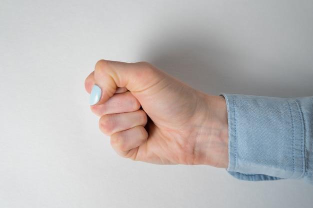 La femme serra la main dans le poing. poing féminin se bouchent, mur blanc.