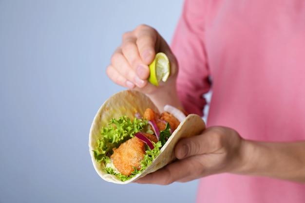 Femme serrant la chaux sur le poisson taco sur fond gris, gros plan
