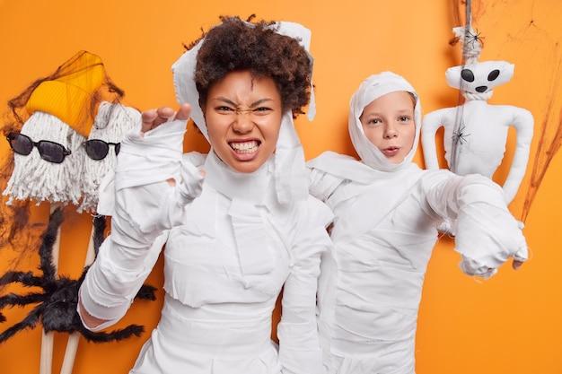Une femme serre les dents avec une expression irritée pose avec une fillette se prépare pour la fête d'halloween vêtue de costumes effrayants entourés de créatures effrayantes
