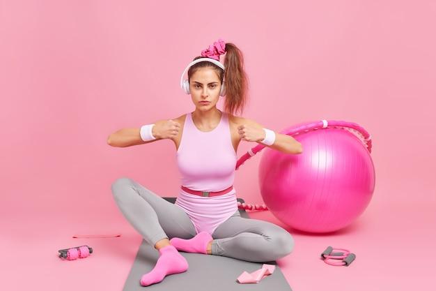 Une femme serre le poing démontre son pouvoir vêtue de vêtements de sport a une queue de cheval écoute de la musique via un casque utilise un équipement de gymnastique pilates. entraînement sportif et mode de vie sain