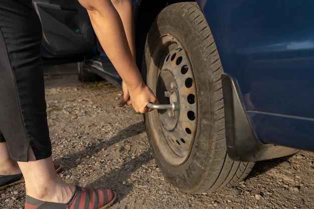 Femme serrer les boulons sur un disque tout en changeant de pneu manuellement sur la roue de voiture