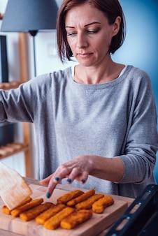 Femme servant des pépites de poulet sur une planche à découper en bois