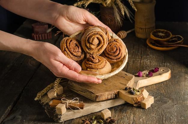 Femme servant des petits pains à la cannelle maison dans une assiette en osier sur un fond sombre, de la nourriture de style sombre