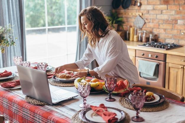 Femme servant la table dans la cuisine.