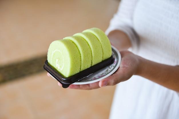 Femme a servi un gâteau vert pandan à la crème