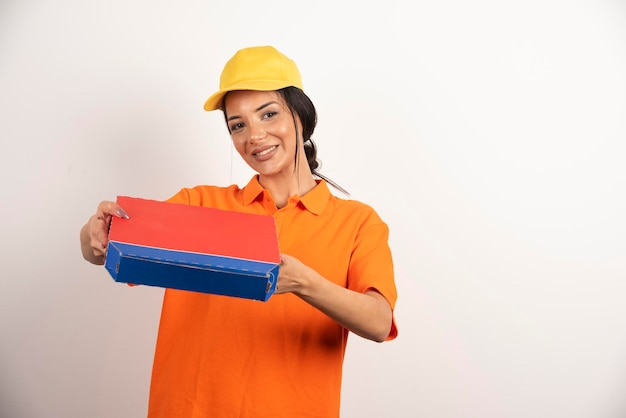 Femme de service de livraison tenant une boîte en carton à pizza.