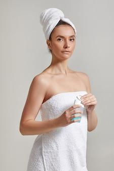 Femme en serviette de bain détient tonique pour enlever le maquillage
